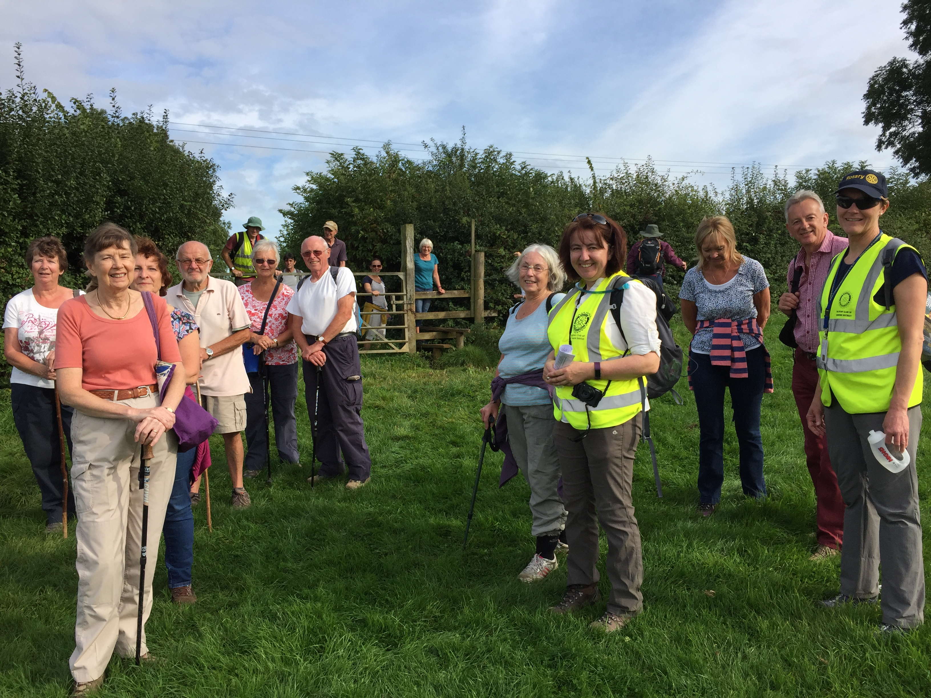 the bounders' crossing a stile into a field with Rotary Members Caroline Dredge and Sarah Holley in the Hi visibility vests